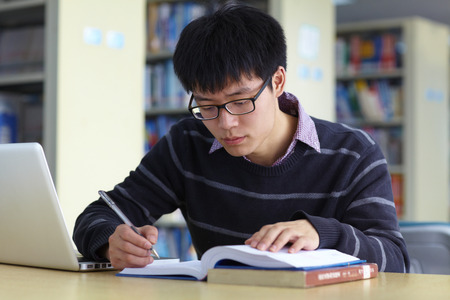 One Young Chinese Male College student study in the library with Laptop