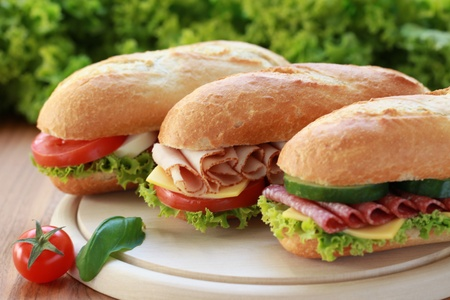 Closeup of three fresh sandwiches with turkey, salami and mozarella