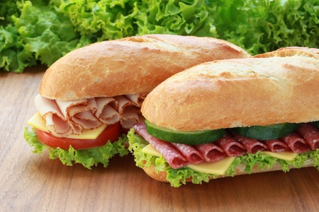 sub sandwich: Closeup of two fresh sandwiches with salami and ham