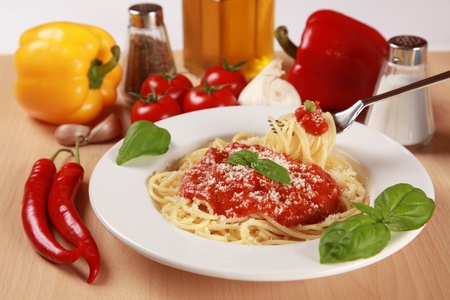 Verse spaghetti worden geserveerd met tomatensaus, basilicum en Parmezaanse kaas.