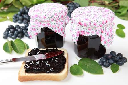 blueberry jam: Two glasses of homemade blueberry jam with fresh fruits, toast and leaves