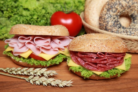 Two fresh bagels with salami and ham aswell as cheese, tomatos and lettuce Stock Photo