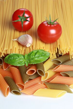 tomatos: Ingredients for a pasta meal including tomatoes, garlic, basil and different kind of pasta
