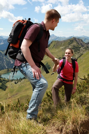 A young male hiker is helping a female hiker to climb a mountain in the German Alps near Oberstdorf.