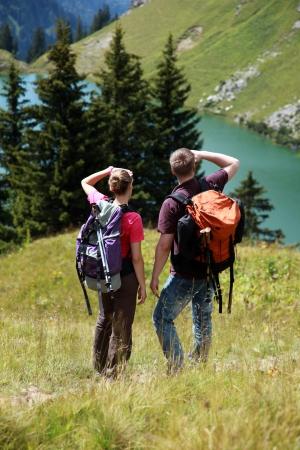 Mannelijke en vrouwelijke wandelaars in de Duitse Alpen in de buurt Oberstdorf zoeken op het juiste spoor.