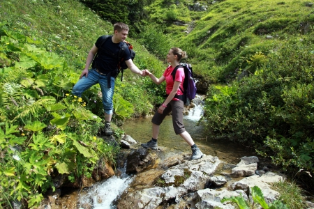 A young male hiker is helping a female hiker to cross a mountain-brook in the German Alps near Oberstdorf. Stock Photo