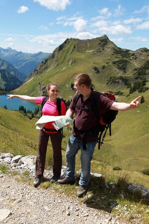 Male and female hikers in the German Alps near Oberstdorf searching the right direction photo