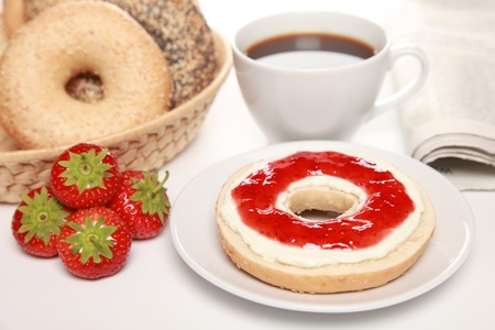 marmelade: Breakfast with fresh bagels served with cream cheese, strawberry marmalade, coffee and a newspaper Stock Photo