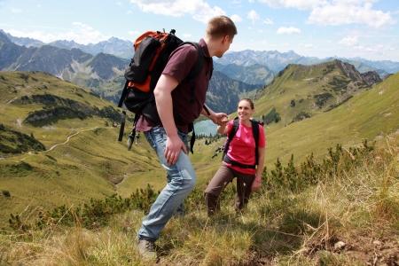 Een jonge mannelijke wandelaar is het helpen van een vrouwelijke wandelaar naar een berg in de Alpen te beklimmen.