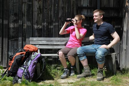 Male and female hikers in the German Alps near Oberstdorf taking a rest and looking through binoculars. photo