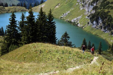 Male and female hikers in the German Alps climbing a hill photo