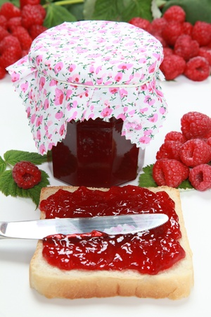 A glass of homemade raspberry jam with a toast, fresh fruits and leaves