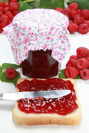 Een glas huisgemaakte frambozenjam met een toast, vers fruit en bladeren