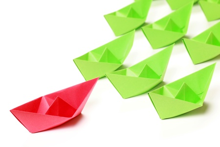 One red and several green paper boats on white background photo