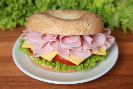 breakfast sandwich: Fresh bagel with ham, tomatos, cheese and lettuce Stock Photo