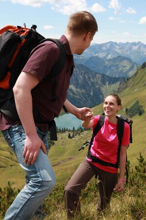 A young male hiker is helping a female hiker to climb a mountain in the German Alps. photo