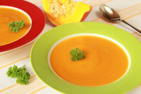 Two Bowls of pumpkin soup and a pumpkin in the background photo