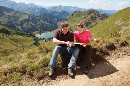 Male and female hikers in the German Alps near Oberstdorf reading a map for orientation. photo