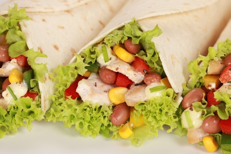 tortillas: Chicken wrap sandwich filled with beans, lettuce and corn