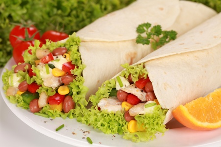 corn tortilla: Two Chicken wrap sandwiches filled with beans, lettuce and corn Stock Photo