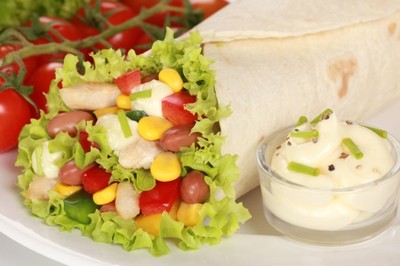 Chicken wrap sandwich filled with beans, lettuce and corn and fresh yoghurt dip photo