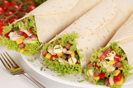 Fresh chicken wrap sandwiches filled with beans, lettuce and corn photo
