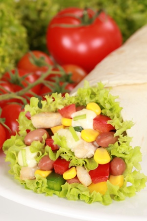 tomatos: Chicken wrap sandwich filled with beans, lettuce and corn