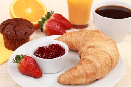 Frans ontbijt met een croissant en aardbeienjam. Geserveerd met koffie, jus d'orange en een muffin.