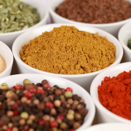 curry powder: Various exotic spices in white bowls. Selective focus on the curry powder.