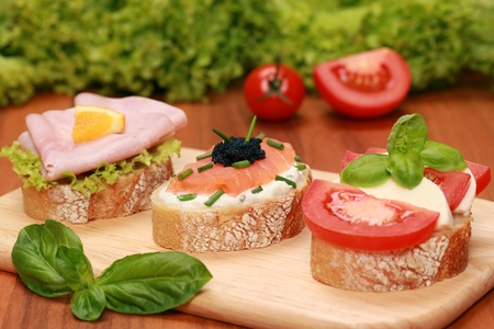 Finger food topped with salmon, ham, mozzarella cheese and tomatoes. photo