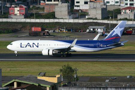boeing: Quito, Ecuador - 16 giugno 2011: LAN jet Boeing 767 con l'HC-CJX registrazione taxi in aeroporto internazionale di Quito (UIO) in Ecuador. LAN Airlines � la compagnia di bandiera del Cile con sede presso l'aeroporto di Santiago. Essa opera con 117 aerei a reazione e c Editoriali