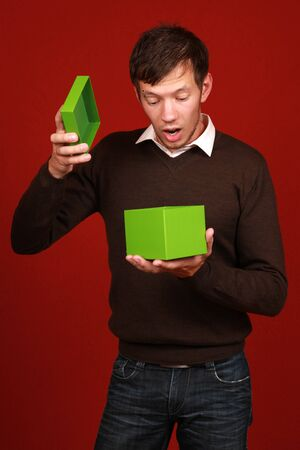 astonished: A young man opens a green box and is surprised Stock Photo