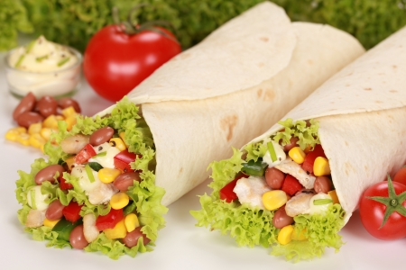 tortillas: Chicken wrap sandwiches filled with beans, lettuce and corn