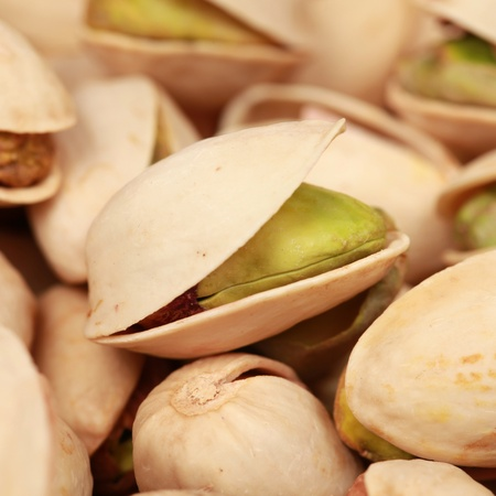 pistachios: Closeup of a pistachio with many other pistachios forming a background