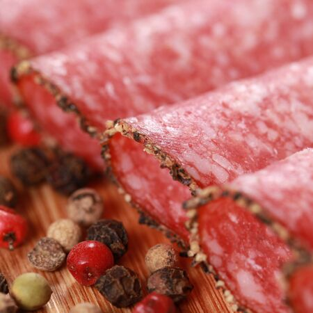 Salami in slices with peppery edge decorated with pepper photo