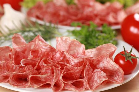 Original Salami from Italy cut in slices served with garlic and tomatoes photo