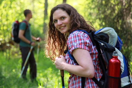 A young woman makes a short break during a Nordic Walking tour photo