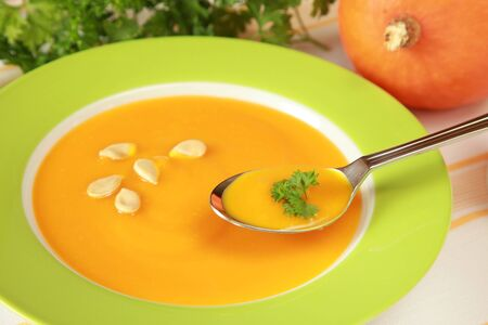 Plate with pumpkin soup and a pumpkin in the background photo