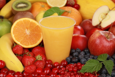 A glass of orange smoothie surrounded by fresh fruits Stock Photo - 14472633