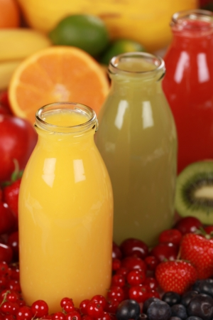 Bottles of different kinds of smoothies surrounded by fresh fruits photo