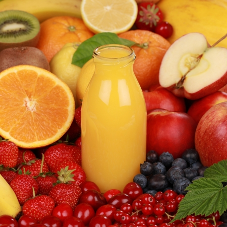 A bottle of orange smoothie surrounded by fresh fruits  Stock Photo - 14472370