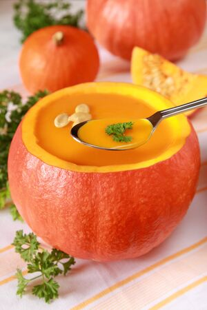 Pumpkin soup in an open pumpkin and more pumpkins in the background. Stock Photo
