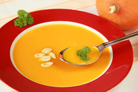 Bowl of pumpkin soup and a fresh pumpkin in the background. photo