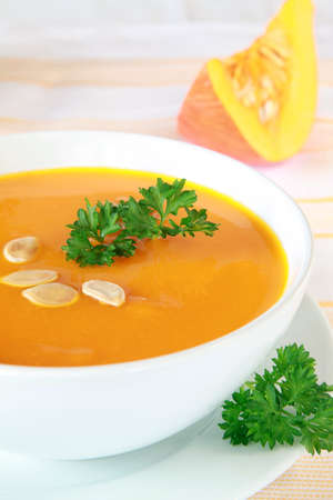 Bowl of pumpkin soup and a fresh pumpkin in the background photo