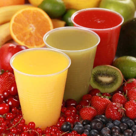 Cups with different kinds of juices surrounded by fresh fruits photo
