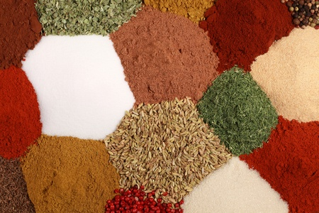 Colorful spices like pepper, paprika, curry and caraway form a background photo