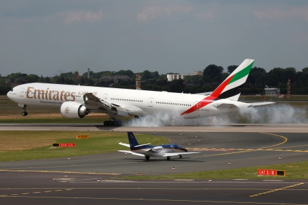 headquartered: Dusseldorf, Germany - July 3, 2012  An Emirates Boeing 777-300ER touches down at Dusseldorf airport in Germany  Emirates is an airline from the United Arab Emirates, headquartered in Dubai  It is the largest airline in the Middle East with 174 aircraft an