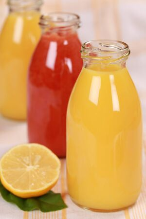 Freshly squeezed juice from oranges and red fruits in bottles photo