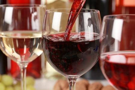 Vino rojo que vierte en un vaso de vino enfoque selectivo en el vino tinto