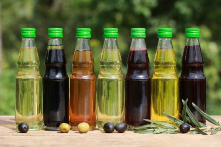 Different types of cooking oil in small bottles on a wooden table photo